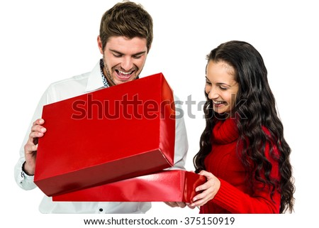 Smiling couple opening gift box on white screen - stock photo