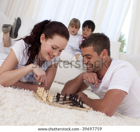 Smiling couple playing chess on floor in living-room with their children on sofa - stock photo