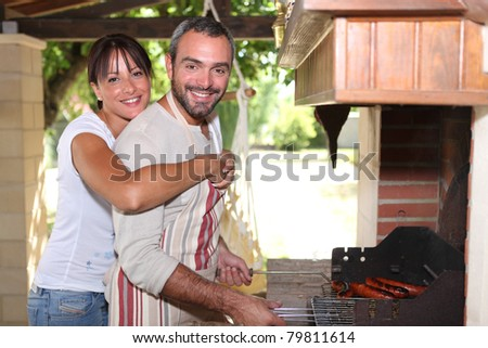 Smiling couple preparing barbecue - stock photo