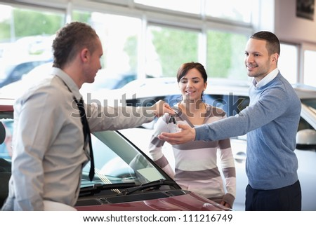 Smiling couple receiving keys from a car dealer in a car shop - stock photo