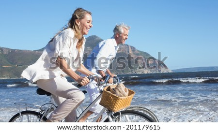 Smiling couple riding their bikes on the beach on a sunny day - stock photo