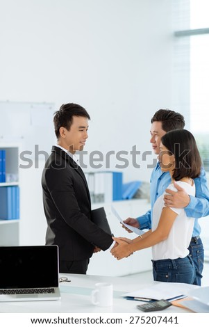 Smiling couple shaking hands with financial advisor - stock photo