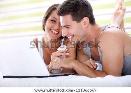 smiling couple shopping on line with credit card from bedroom - stock photo