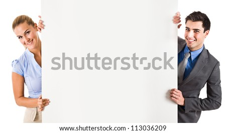 Smiling couple showing a blank board - stock photo
