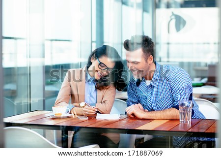Smiling couple sitting at a table and taking notes - stock photo