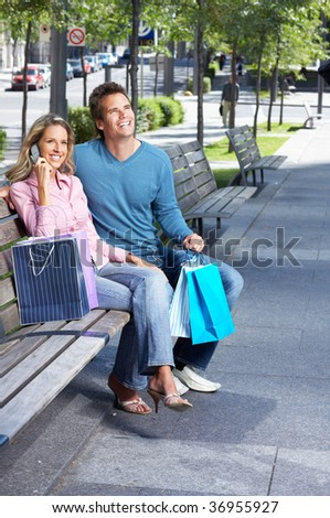 smiling couple sitting in the park after shopping