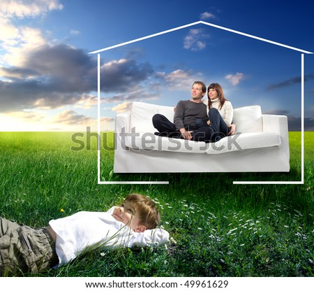 Smiling couple sitting on a couch and happy child lying on green meadow - stock photo