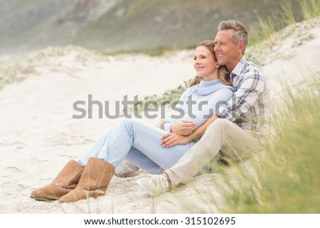 Smiling couple sitting together at the beach - stock photo