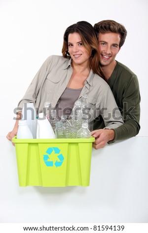 Smiling couple sorting garbage on white background - stock photo