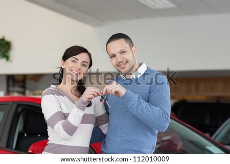 Smiling couple standing next to a car while holding keys - stock photo