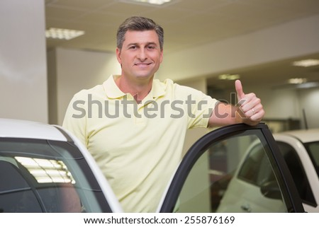 Smiling couple standing while giving thumbs up at new car showroom - stock photo