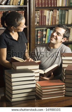 Smiling couple surrounded by books in a library. Vertically framed photo. - stock photo
