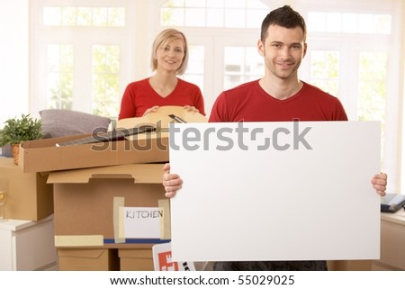 Smiling couple surrounded with boxes in new house, copyspace on blank poster. - stock photo