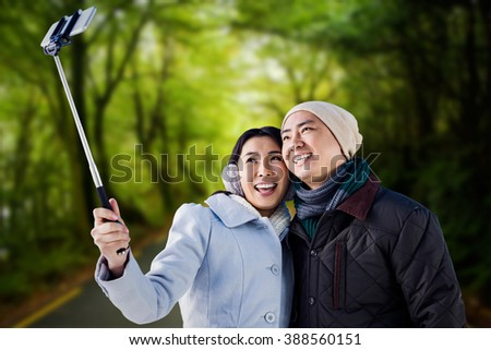 Smiling couple taking selfie against country road - stock photo