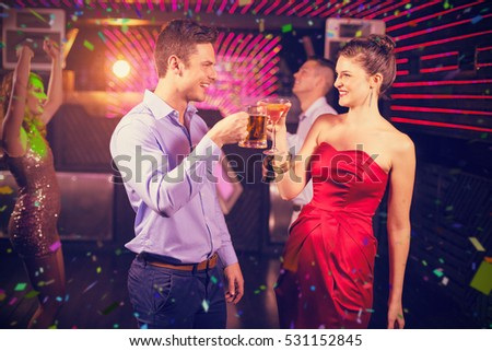 Smiling couple toasting glass of beer and cocktail against flying colours