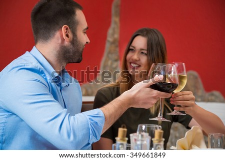 Smiling couple toasting with wine in restaurant. Smiling girl and her boyfriend celebrating in restaurant.