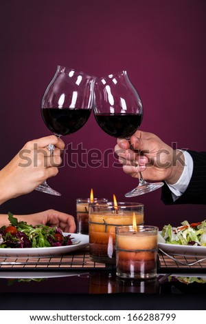 Smiling Couple Tossing Wine Glass While Having Dinner - stock photo