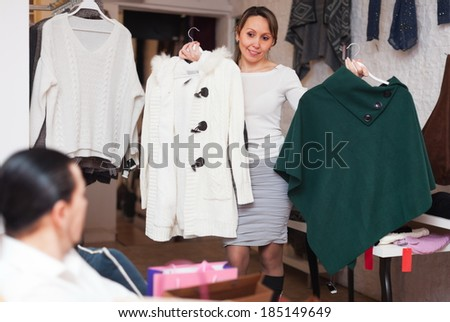 Smiling couple trying coat in fitting-room at clothing store - stock photo