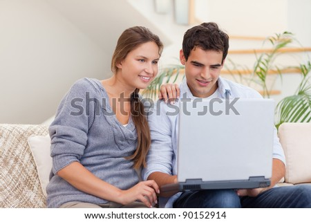 Smiling couple using a laptop in their living room