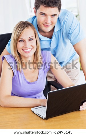 Smiling couple using computer on the desk looking at the camera - stock photo
