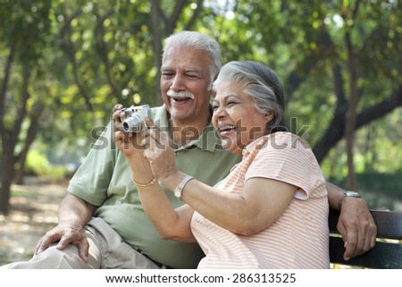 Smiling couple using digital camera at park - stock photo