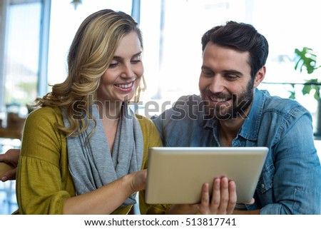 Smiling couple using digital tablet in cafe