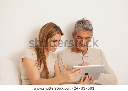 Smiling couple using the ipad - stock photo
