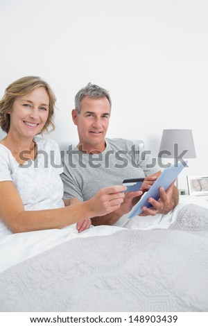 Smiling couple using their tablet pc to buy online looking at camera at home in bedroom - stock photo