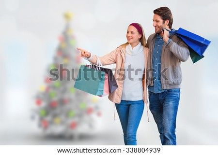 Smiling couple walking hand in hand and going window shopping against blurry christmas tree in room - stock photo