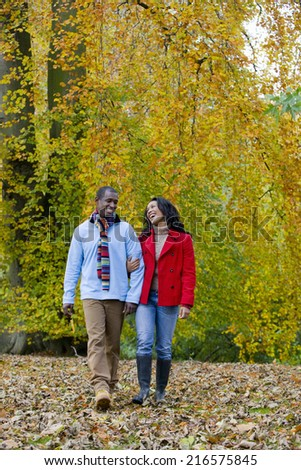 Smiling couple walking in park among autumn leaves - stock photo