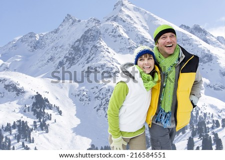 Smiling couple walking with mountain in background - stock photo