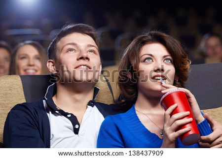Smiling couple watching movie at the cinema - stock photo