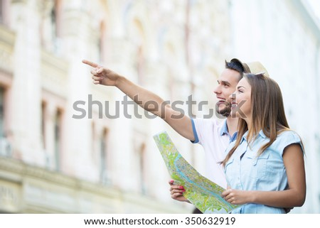 Smiling couple with a map on the street - stock photo