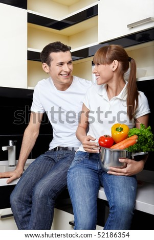Smiling couple with capacity with vegetables on kitchen - stock photo
