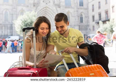 Smiling couple with luggage reading the map at street in sunny day - stock photo