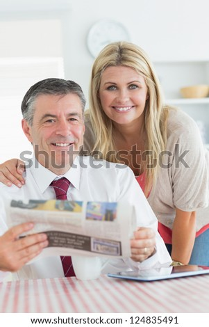 Smiling couple with newspaper and tablet pc in the kitchen before work - stock photo