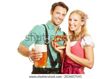 Smiling couple with pretzel and beer at Oktoberfest in Bavaria - stock photo