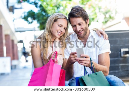 Smiling couple with shopping bags sitting and using smartphone at shopping mall - stock photo