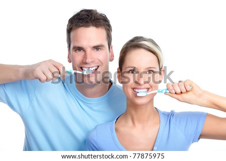 Smiling couple with toothbrushes. Over white background