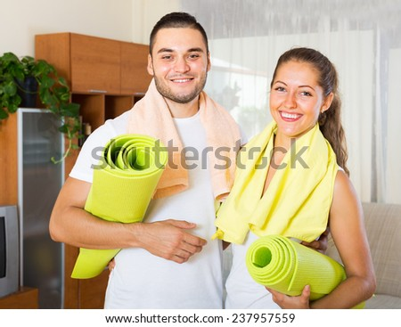 Smiling couple with towels before yoga class at home - stock photo