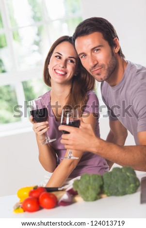 Smiling couple with wine and vegetables in kitchen
