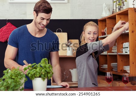 Smiling couple working as a team in the kitchen with the husband stirring the pot on the stove as his wife fetches the crockery and glassware for the meal - stock photo