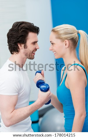 Smiling couple working out together in the gym lifting weights exercising with dumbbells as they look into each others eyes in motivation - stock photo