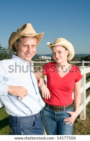 Smiling cowboy and cowgirl leaning against a fence. Vertically framed photograph. - stock photo