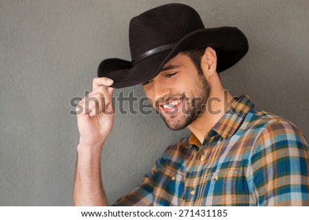 Smiling cowboy. Handsome young man adjusting his cowboy hat and smiling while standing against grey background  - stock photo