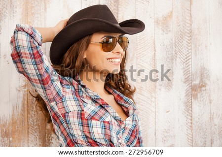 Smiling cowgirl. Beautiful young cowgirl adjusting her hat and smiling while standing against the wooden background - stock photo