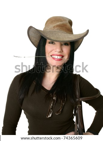 Smiling cowgirl wearing a leather western hat and carrying bridle. - stock photo
