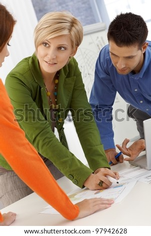 Smiling coworkers brainstorming, using notes, working together, standing at meeting table. - stock photo
