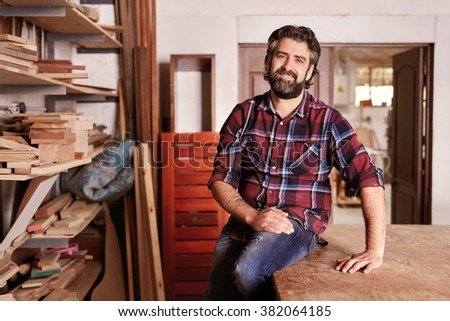 Smiling craftsman sitting in his woodwork studio for a portrait, with shelves of different  pieces of wood, where he works as a carpenter - stock photo
