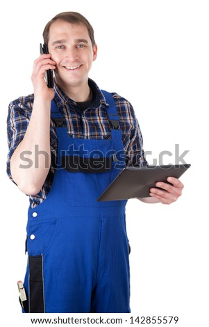 Smiling craftsman with mobile phone and digital tablet - stock photo